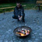 Das Bild zeigt einen Mann, der ein Marshmallow über dem Feuer röstet.