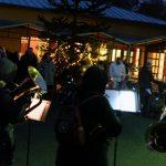 Das Bild zeigt die Musiker und einige der Gäste vor dem erleuchteten Pflanzraum.