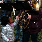 Das Bild zeigt ein Kind, das mit den Musikern spricht.