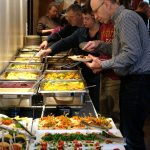 Das Bild zeigt Menschen, die sich am Büffet Essen holen.