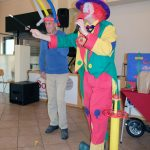 Das Bild zeigt den Clown und einen Mann, der einen Hut aus Luftballons trägt.