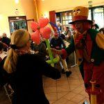 Das Bild zeigt, wie der Clown einer Frau eine Blume aus Luftballons überreicht.