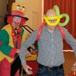 Das Bild zeigt den Clown und einen Mann, dem der Clown eine Taucherausrüstung aus Ballons anlegt.