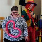 Das Bild zeigt den Clown und eine Frau, die ein Herz aus Luftballons hält.