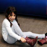 Das Bild zeigt ein Mädchen, das sich die Schuhe anzieht.