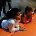 Das Bild zeigt zwei Kinder, die den anderen zuschauen.