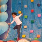 Das Bild zeigt ein Mädchen an der Kletterwand.