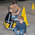 Das Bild zeigt zwei Jungen und einen Betreuer mit einem Pedalo.