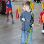 Das Bild zeigt einen Jungen beim Bogenschießen.