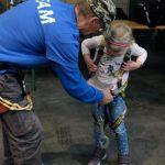 Das Bild zeigt ein Kind beim Anlegen der Kletterausrüstung.