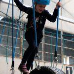 Das Bild zeigt ein Kind auf einem Kletterparcours.