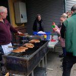 Das Bild zeigt den Grill und Besucher, die Bratwurst kaufen.