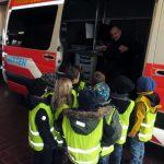 Das Bild zeigt, wie Feuerwehrmann Markus den Kindern ein Einsatzfahrzeug erklärt.