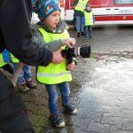 Das Bild zeigt einen Jungen, der einen Feuerwehrschlauch hält.