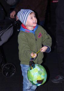 Das Bild zeigt einen lachenden Jungen mit seiner Laterne.