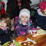 Das Bild zeigt drei Kinder beim Essen.