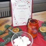 """Das Bild zeigt eine Schale mit Würfelzucker, Weihnachtsdekoration und ein hübsch gestaltetes Rezept für """"Weihnachtsglück""""."""