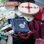 Das Bild zeigt kleine Stofftaschen, Bretter mit Glasperlen und gestrickte Hausschuhe.