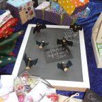 Das Bild zeigt eine Pinwand mit kleinen Fledermäusen aus Holz.