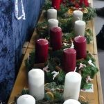 Das Bild zeigt viele hintereinander aufgereihte Adventskränze.