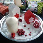 Das Bild zeigt einen silbernen Teller mit Kunstschnee, Häuschen und einer Kerze.