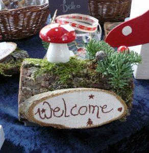 Das Bild zeigt ein Willkommensschild mit einem Fliegenpilz aus Keramik.