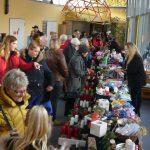 Das Bild zeigt zahlreiche Besucher an einem langen Verkaufsstand.