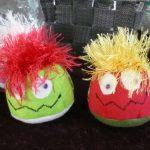 Das Bild zeigt zwei bunte Stressbälle mit lustigen Gesichtern und Haaren.